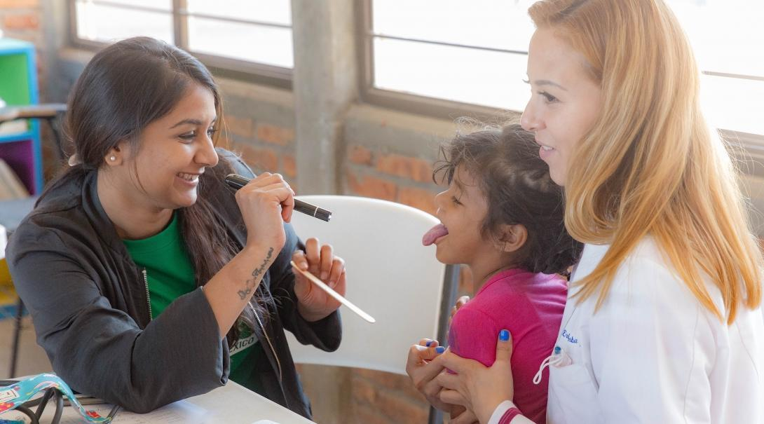 Projects Abroad intern examines a young girl's throat at a medical outreach during a dental placement in Mexico.